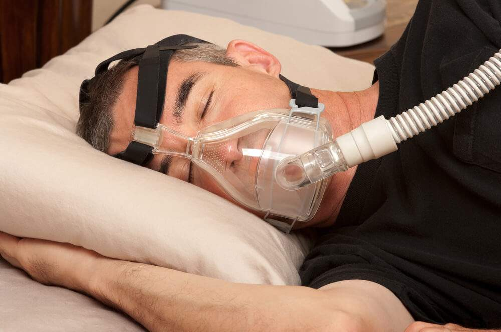 A man is using a CPAP device for sleep apnea