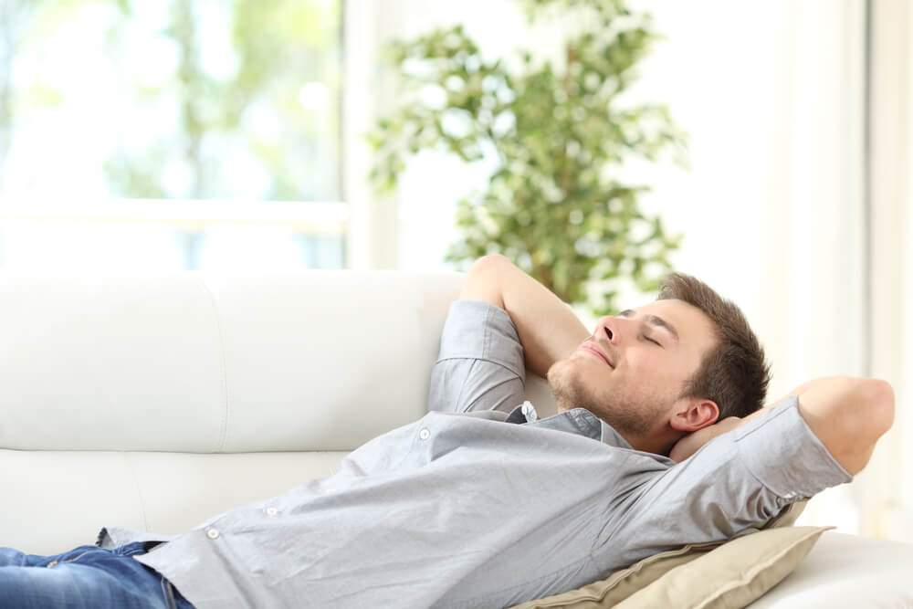 A rested man is lying on a couch