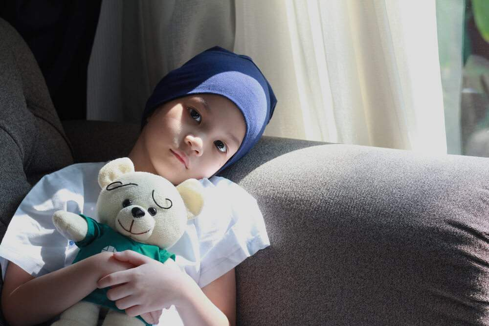A child is holding a plush toy and getting prepared for chemotherapy