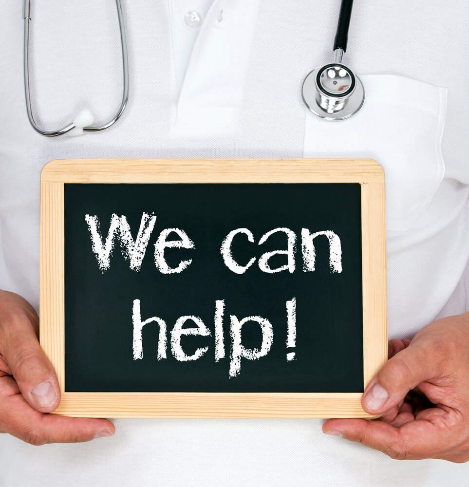A doctor is holding a sign that says 'we can help'