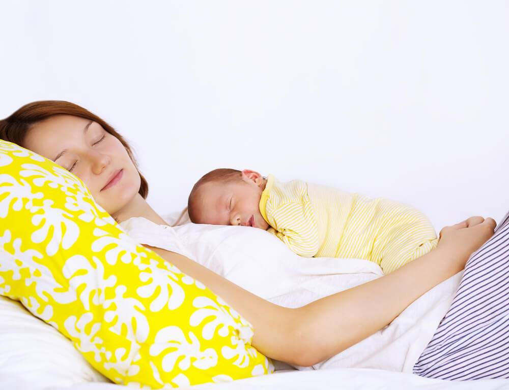 A mom and her newborn baby are sleeping