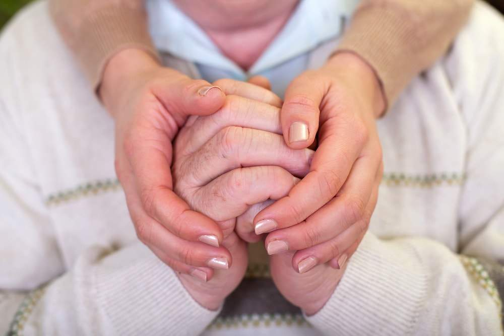A woman is holding the hands of a dementia patient