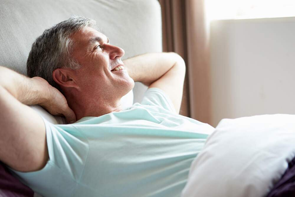 A happy man is lying in bed