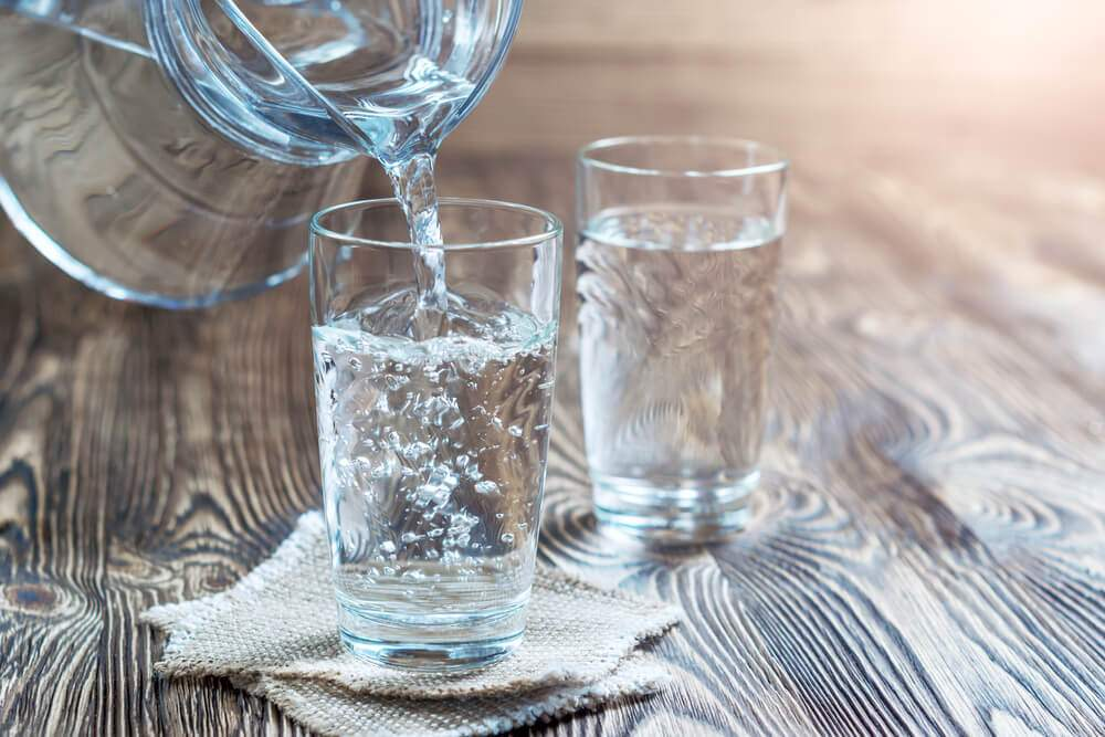 Two glasses of magnetic water on a wood table