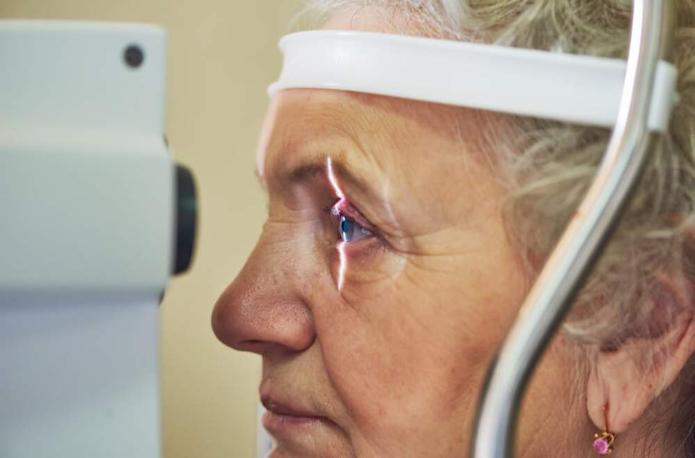 An elderly woman is getting a glaucoma test